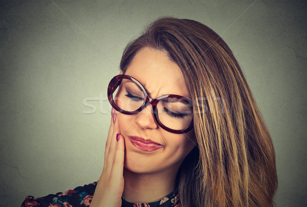 woman in glasses with sensitive toothache crown problem about to cry from pain  Stock photo © ichiosea