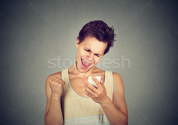 Happy man looking at mobile phone pumping fist celebrates success Stock photo © ichiosea