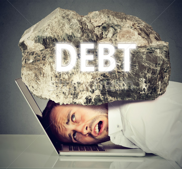 man squeezed between laptop and rock. Student loan debt concept Stock photo © ichiosea
