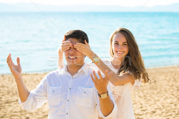 Beautiful woman covering eyes of boyfriend smiling while both standing outdoors Stock photo © ichiosea