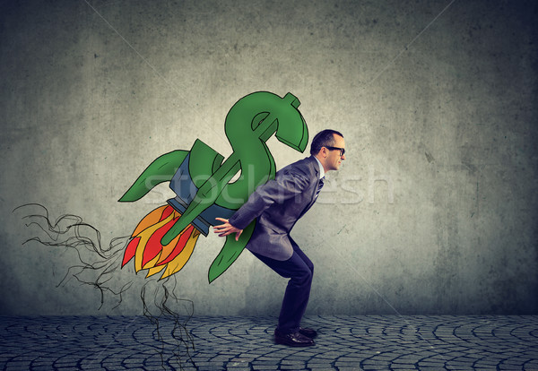Ambitious mature business man with high financial goals and dollar rocket on his back Stock photo © ichiosea