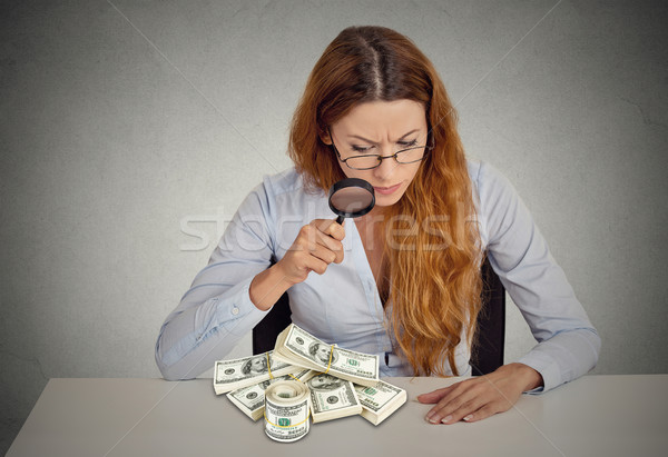 woman looking through magnifying glass on stack of dollar banknotes Stock photo © ichiosea