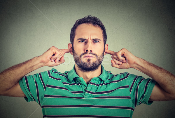 headshot displeased young man plugging ears with fingers doesn't want to listen Stock photo © ichiosea