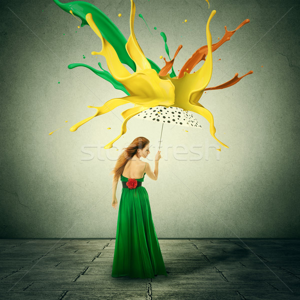Beautiful woman in green dress with umbrella as shelter against colorful drops splashes of paint fal Stock photo © ichiosea