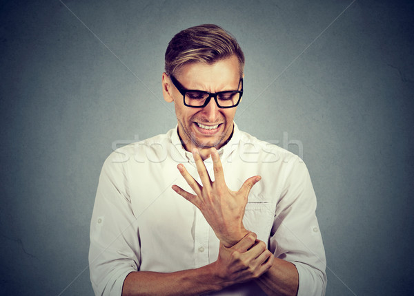 man holding painful wrist arm. Sprain pain Stock photo © ichiosea