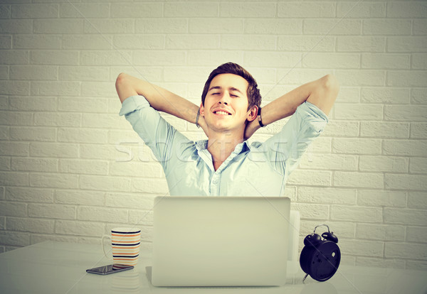 Relaxed man with laptop sitting at desk brick wall background Stock photo © ichiosea