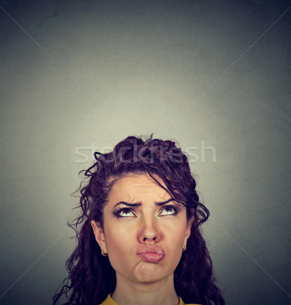 Doubtful perplexed young woman looking up  Stock photo © ichiosea