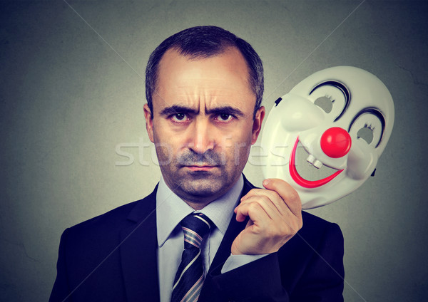 Angry business man taking off happy clown mask   Stock photo © ichiosea