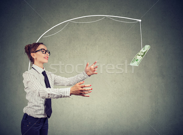 Woman trying to catch dollar bill Stock photo © ichiosea