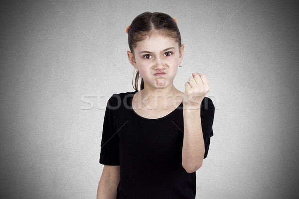 Angry little girl showing fist to someone Stock photo © ichiosea