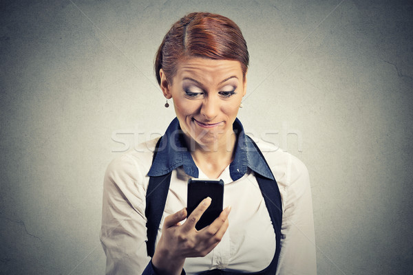 displeased young businesswoman reading bad news on smart phone Stock photo © ichiosea