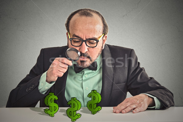 Business man looking through magnifying glass at dollar signs  Stock photo © ichiosea