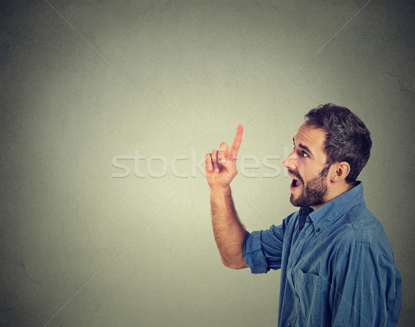 young man has an idea, pointing with finger up looking up Stock photo © ichiosea