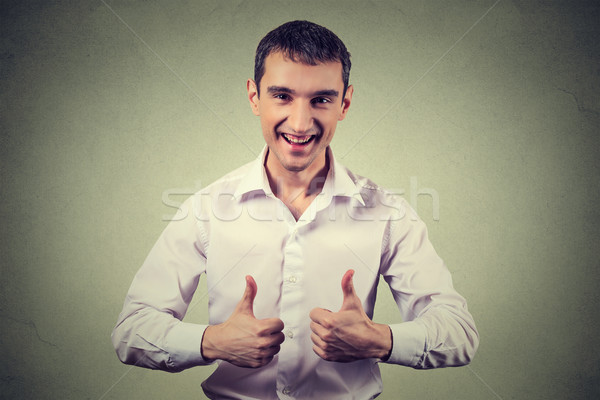 Happy man giving thumbs up sign. Positive human face expression body language Stock photo © ichiosea