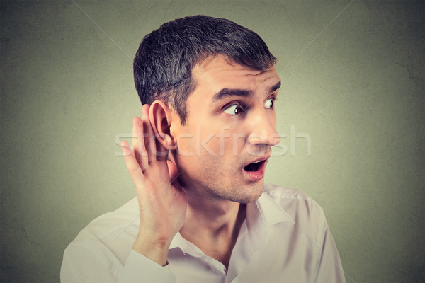 man placing hand on ear asking someone to speak up or listening carefully to gossip Stock photo © ichiosea