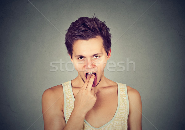 disgusted man with finger in mouth displeased ready to throw up  Stock photo © ichiosea