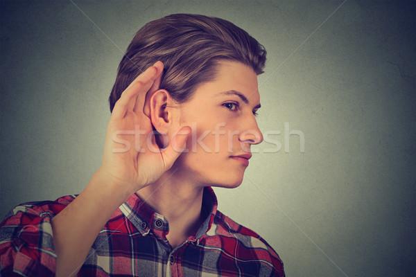 Listening man holds his hand near ear gesture  Stock photo © ichiosea
