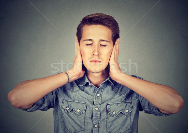 tranquil, relaxed young man covering ears, eyes closed Stock photo © ichiosea