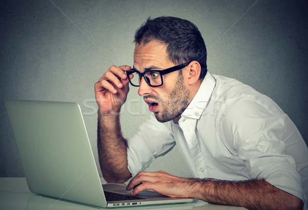 Young shocked man using laptop computer sitting at table Stock photo © ichiosea