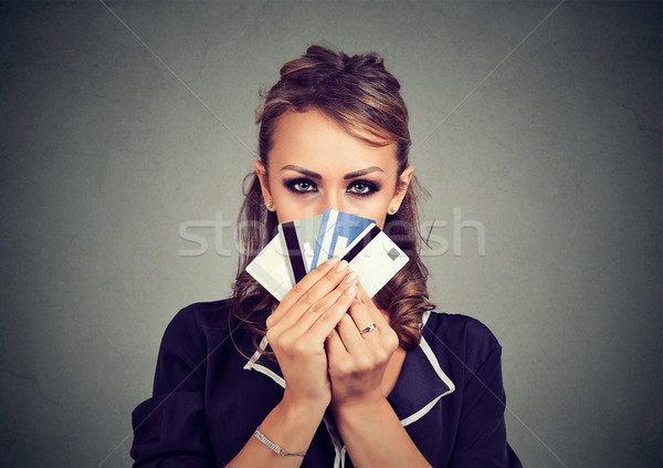 Serious woman hiding face behind many credit cards Stock photo © ichiosea
