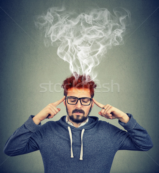 man thinking very intensely having headache with steaming coming out Stock photo © ichiosea