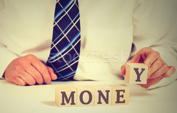 Financial market concept. Businessman arranging wooden blocks with word money Stock photo © ichiosea