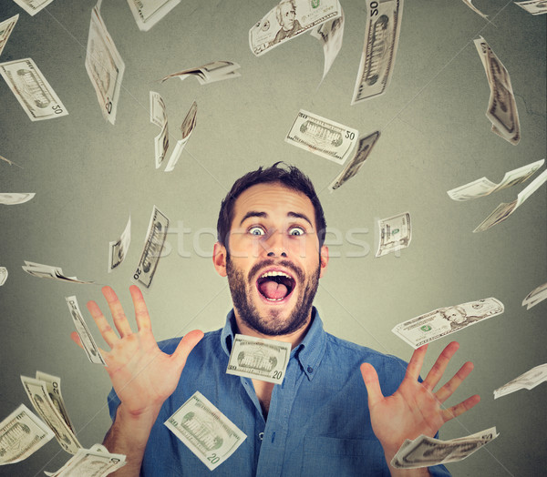 Happy young man going crazy screaming super excited under money rain  Stock photo © ichiosea