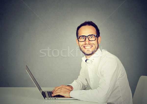 Smiling young man using a laptop Stock photo © ichiosea