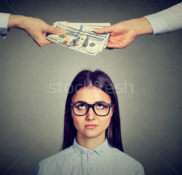 Worried sad woman looking up at hands exchanging money Stock photo © ichiosea