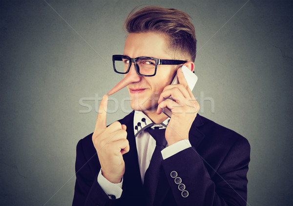 young sly man with long nose talking on mobile phone. Liar concept.  Stock photo © ichiosea