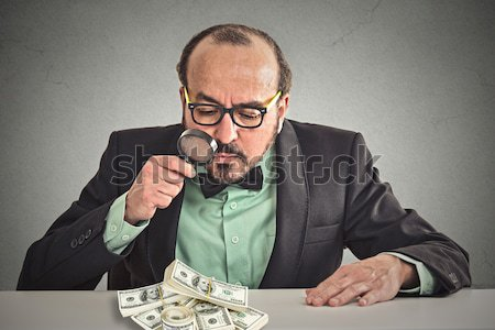 Business man looking through magnifying glass on stack of dollar banknotes Stock photo © ichiosea
