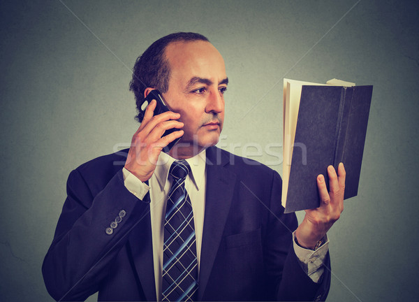 business man in suit, executive reading book talking on smart phone Stock photo © ichiosea
