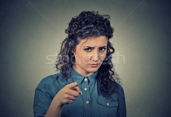 angry young woman pointing at camera isolated on gray background Stock photo © ichiosea