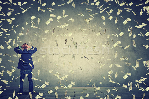 business man standing in front of wall under money rain dollar banknotes falling down Stock photo © ichiosea