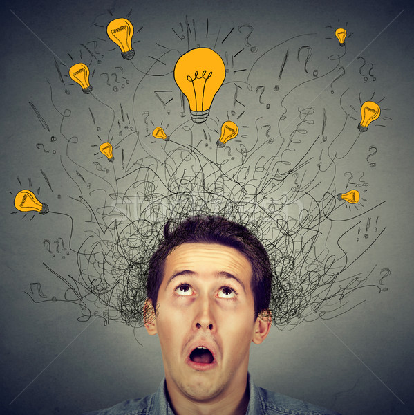 Surprised man with many ideas light bulbs above head looking up  Stock photo © ichiosea