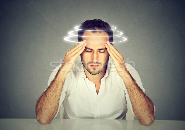 Man with vertigo. Young patient suffering from dizziness. Stock photo © ichiosea