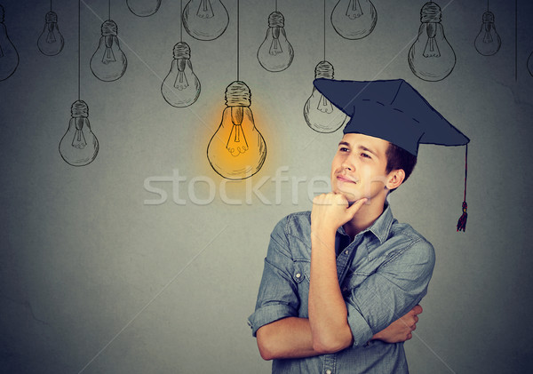 Thoughtful student in cap gown looking up at light bulb Stock photo © ichiosea