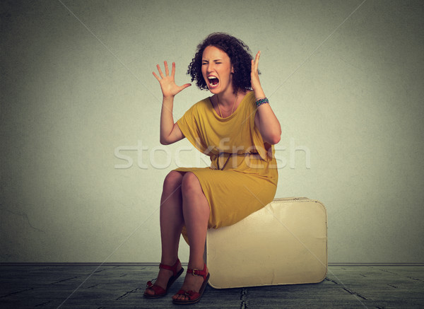 Stressed woman sitting on a suitcase screaming in frustration. Stock photo © ichiosea