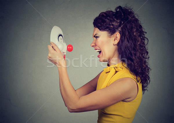 Side profile of an angry woman screaming at happy clown mask  Stock photo © ichiosea