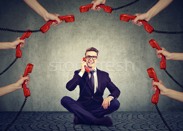 Stock photo: Business communications customer support concept. Businessman always on the telephone answering many
