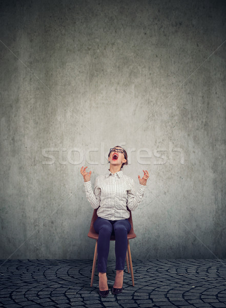 Stressed woman company employee sitting on a chair screaming in desperation  Stock photo © ichiosea