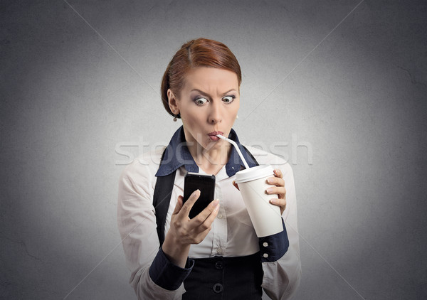 surprised woman reading news on smartphone drinking soda  Stock photo © ichiosea