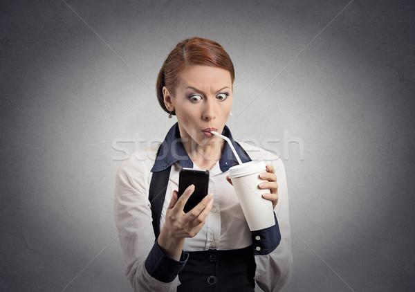 удивленный женщину чтение Новости смартфон питьевой Сток-фото © ichiosea