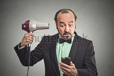woman reading news on smartphone holding hairdryer Stock photo © ichiosea
