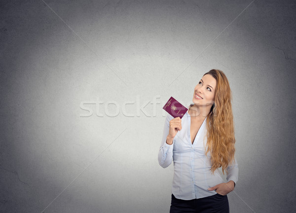 smiling happy woman standing holding passport looking up imagining new life Stock photo © ichiosea