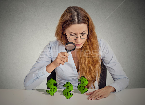 Business woman looking through magnifying glass at dollar signs  Stock photo © ichiosea