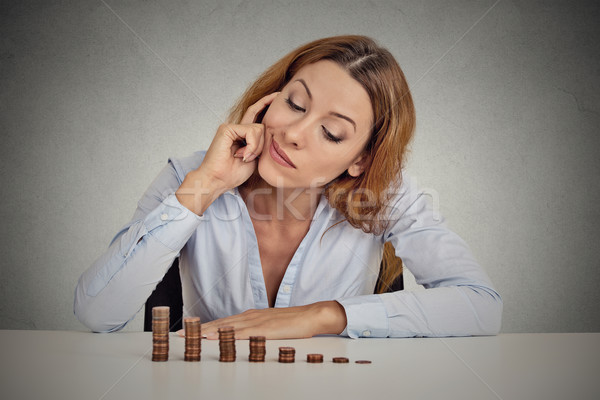 business woman corporate executive sitting at table with growing stack of coins Stock photo © ichiosea