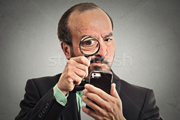 man looking through a magnifying glass on smartphone Stock photo © ichiosea