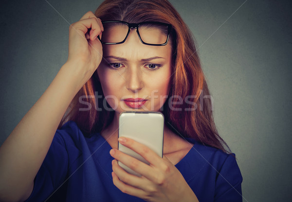 young woman with glasses having trouble seeing cell phone has vision problems Stock photo © ichiosea