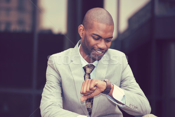 Handsome businessman looking at his watch sitting outdoors  Stock photo © ichiosea